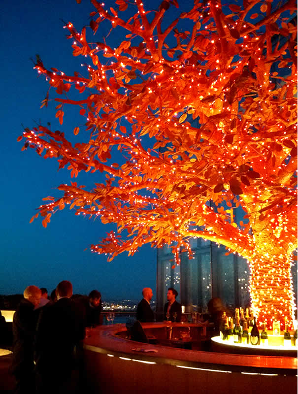 Escultura iluminanda de naranjo en la terraza oeste de SushiSamba