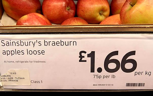 Manzanas a la venta en Sainsbury's mostrando el precio por kilo y por libra