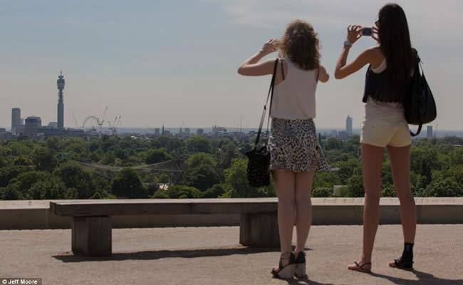 Chicas contemplando skyline de Londres bajo el sol
