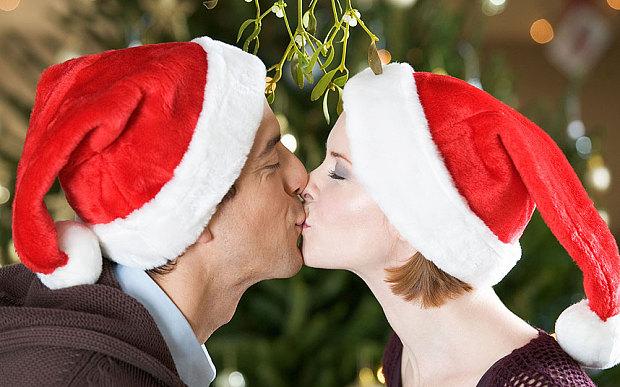 Hombre y mujer besándose bajo una rama de muérdago